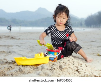 Happy child playing with sand at the beach