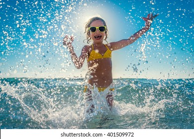 Happy child playing in the sea. Kid having fun outdoors. Summer vacation and healthy lifestyle concept
