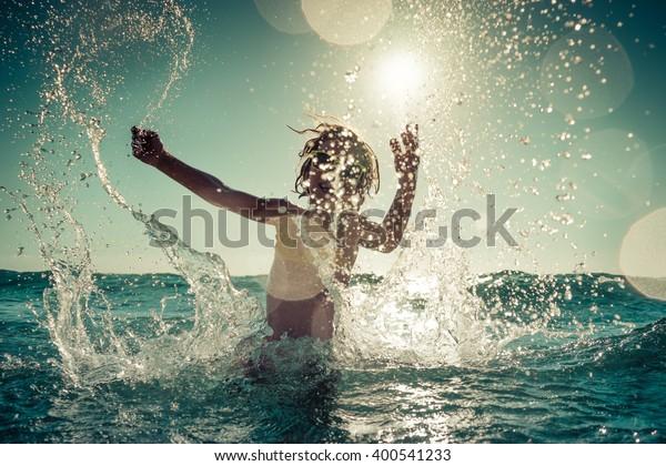 Glückliches Kind, das im Meer spielt. Kinder, die sich draußen amüsieren. Sommerurlaub und gesundes Lebensstil-Konzept. Tonbild