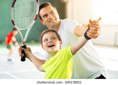 Happy child playing sport game with his parent