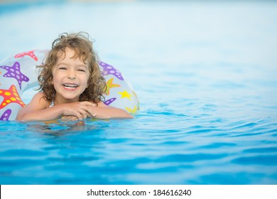 Happy child playing in swimming pool. Summer vacations concept