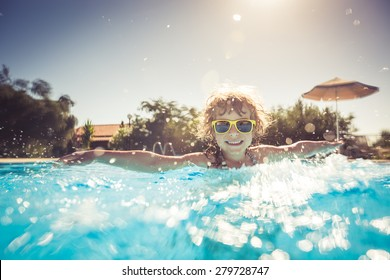 Happy child playing in swimming pool. Summer vacation concept