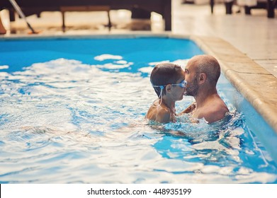 Happy child playing in swimming pool with father. Summer vacation concept