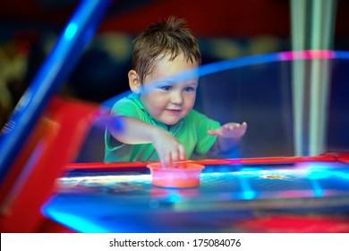 happy child playing table air hockey at fair