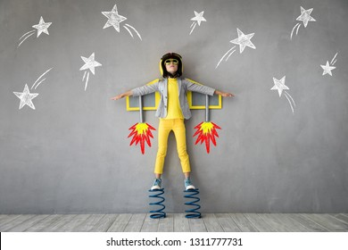 Happy child playing with toy jet pack. Kid pilot ready to fly. Success, innovation and leader concept