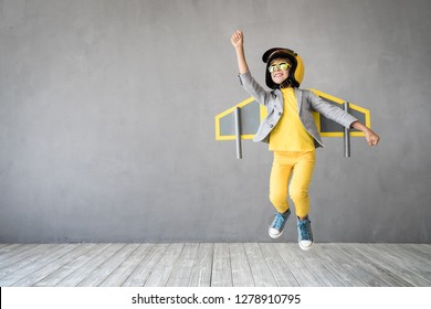Glückliches Kind, das mit Spielzeugjetpack spielt. Ein Kinderpilot, der sich zu Hause amüsiert. Erfolg, Innovation und Leitkonzept