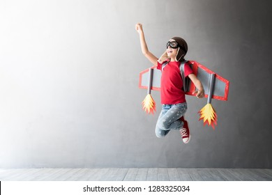 Happy child playing with toy jetpack. Kid pilot having fun at home. Success, innovation and leader concept
