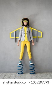 Happy child playing with toy jetpack. Kid pilot standing on spring. Success, innovation and leader concept