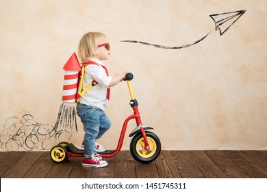 Happy child playing with toy rocket at home. Funny kid driving scooter. Success and win concept