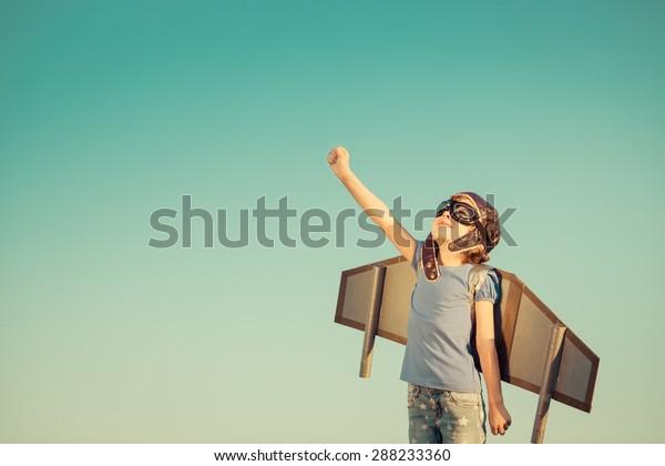 Niño feliz jugando con alas de juguete contra el fondo del cielo de verano. Tono retro