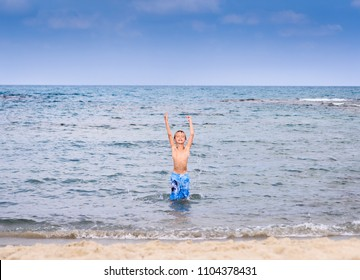 Happy child playing with water in the sea. Kid having fun outdoors. Summer vacation and healthy lifestyle concept.
