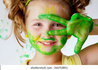Happy child plays in the paint at home during the renovation.
