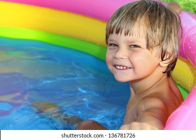 Happy child in the pool with a cheerful smile.