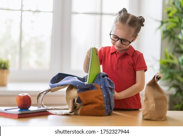 Happy child preparing for school. Little girl is putting things into backpack.