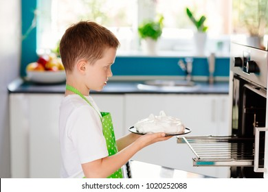 Happy child putting cake to oven . Child helping in kitchen