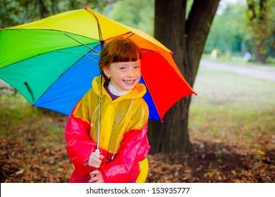 happy child in the rain with a bright umbrella