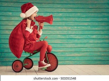 Happy child rides a bike. Kid playing at home. Christmas Xmas winter holiday concept