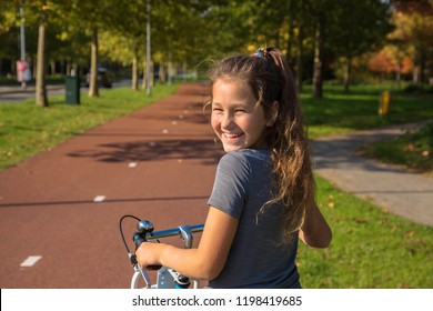 Happy child rides a bike on bike path. Cyclist child or teenager girl enjoys good weather and cycling. Environmentally friendly transport concept. Girl is smiling and laughs. Netherlands, Holland.