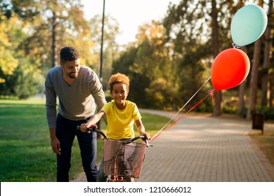Happy child riding a bicycle. Father teaching his daughter how to ride a bike. Birthday present, balloons flying.
