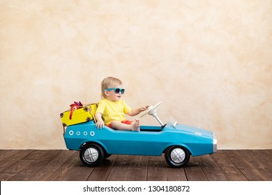 Happy child riding toy vintage car. Funny kid playing at home. Summer vacation and travel concept