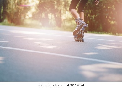 Happy child rollerblading on a sunny day - tarmac lane in park