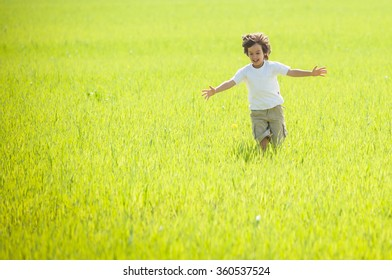 Happy child running on beautiful green yellow grass field