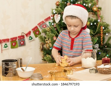 Happy child in Santa Claus hat is preparing cookies for Christmas. A small assistant knead the dough. Christmas tree in the background. Selective focus