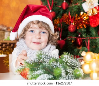 Happy child in Santa hat against Christmas tree with decorations