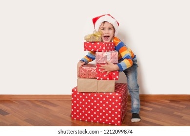 Happy child in Santa red hat holding Christmas presents on a white background. Christmas time.