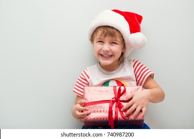 Happy child in Santa red hat holding Christmas present. Christmas time.