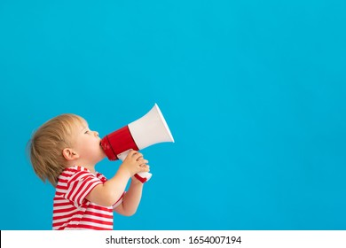 Happy child shouting by megaphone against blue background. Kid having fun on summer vacation.
