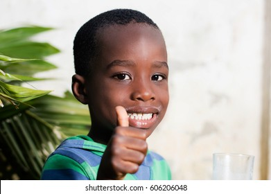 Happy child in a sign of appreciation after drinking a glass of milk.
