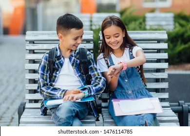 Happy child sit on bench, playing with smart watch with  smile. Learning new technology together. Lifestyle.