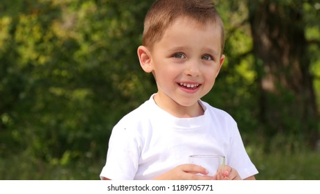 Happy child sitting in the background of nature and drinking berry juice. Cute boy smile and laugh.
