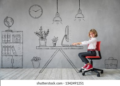 Happy child sitting at the desk in imaginary office. Business or education concept