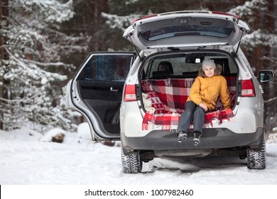 Happy child sitting inside of car trunk for luggage. Winter evergreen forest with huge snow covered pines. Copyspace