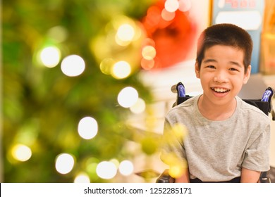 A happy child sitting on a wheelchair with blurred lighting .
