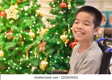 A happy child sitting on a wheelchair with blurred lighting and Christmas trees.