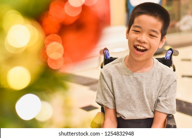 A happy child sitting on the wheelchair with blurred lighting .