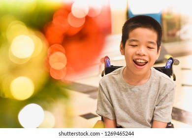 A happy child sitting on the wheelchair with blurred lighting . Happy disabled child concept.