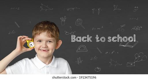 Niño feliz con un pequeño reloj cerca de un colegio con inscripciones. De vuelta a la escuela, concepto de educación.