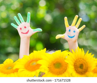 Happy child with smile on hands against green spring background