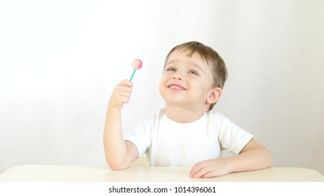 Happy child smiling and eating lollipops on a stick, sitting at a table on a white background - 6