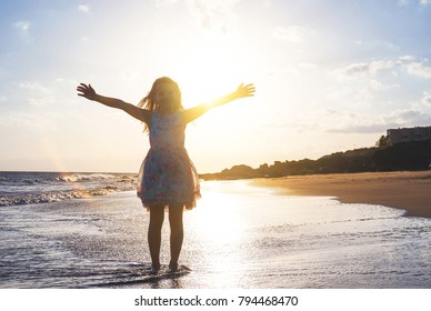 Happy child spreading her hands up on the beach on a magnificent sunset - Baby girl having fun in vacation holidays - Childhood, children, happiness concept