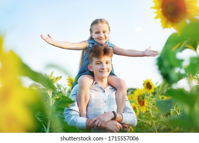 Happy child in spring sunflower field. Little girl sits on the elders of the elder brother.  Freedom concept