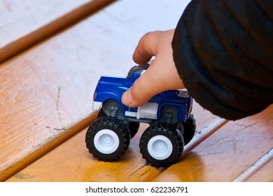 Happy child stretching out his hands to grab blue car toy on yellow wooden boards on the playground outdoors. Shallow depth of focus.