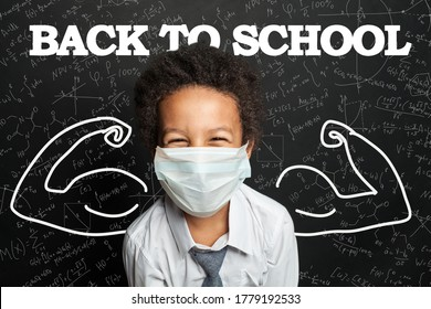 Happy child student in medical protective face mask on blackboard background
