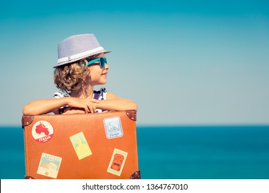 Happy child with suitcase on the beach. Kid enjoys a summer vacation at the sea. Travel and holiday concept