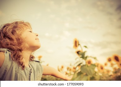 Happy child in sunflower field. Freedom concept