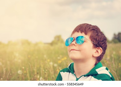 Happy child in sunglasses on the field with dandelions. Boy looking to the sky in summer outdoors